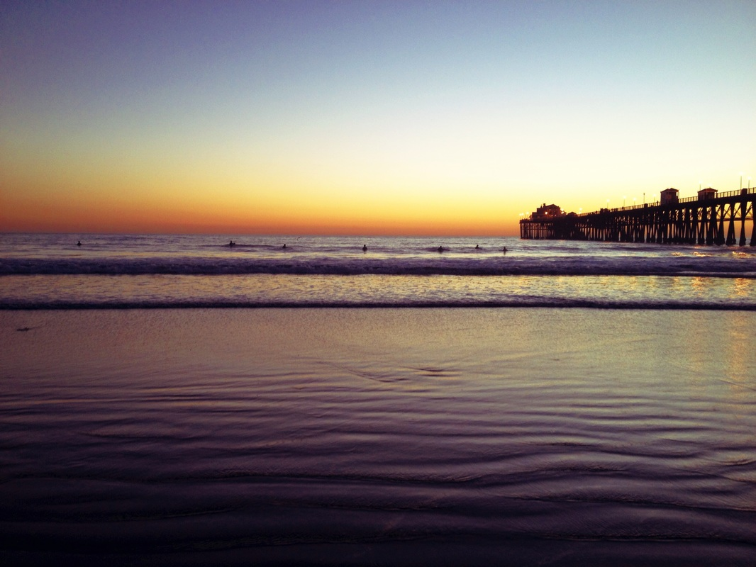 Oceanside beach at Sunset in California. Look at the little surfers!